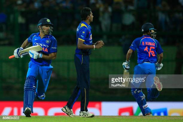 Indian cricketers M S Dhoni and Bhuvneshwar Kumar run between the wickets during the 2nd One Day International cricket match between Sri Lanka and...