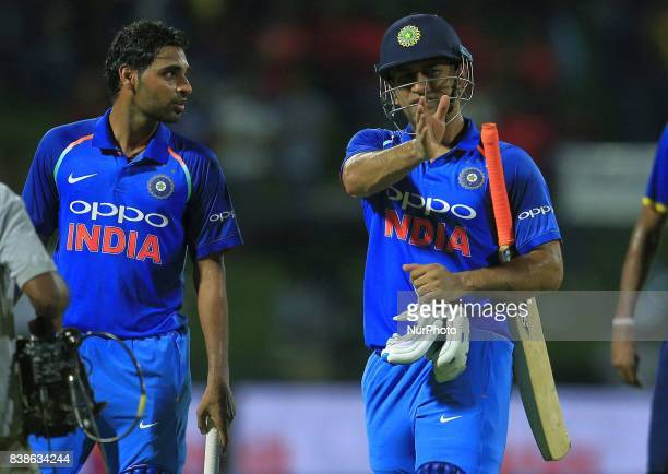 Indian cricketers M S Dhoni and Bhuvneshwar Kumar walk back after securing a 3 wicket victory during the 2nd One Day International cricket match...