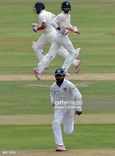 Indian cricketers Rohit Sharma and Shikhar Dhawan run between wickets as Sri Lanka Board President's XI cricketer Kaushal Silva fields during the...