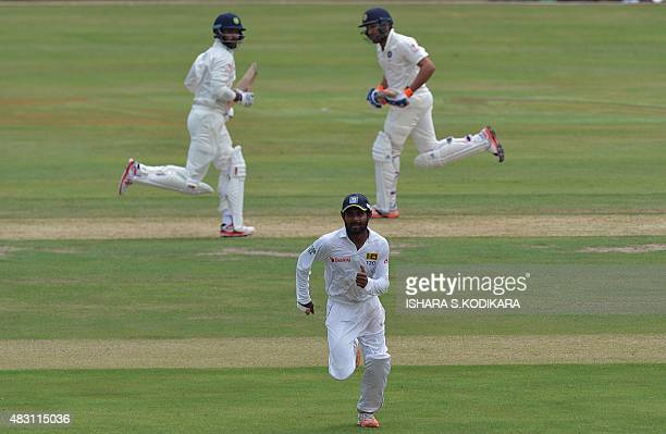 Indian cricketers Rohit Sharma and Shikhar Dhawan run between wickets as Sri Lanka Board President's XI cricketer Kaushal Silva fields during the...