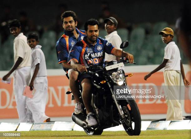 Indian cricketers Rohit Sharma and Virat Kohli ride a motorcycle on the pitch after a presentation ceremony following the second One Day...