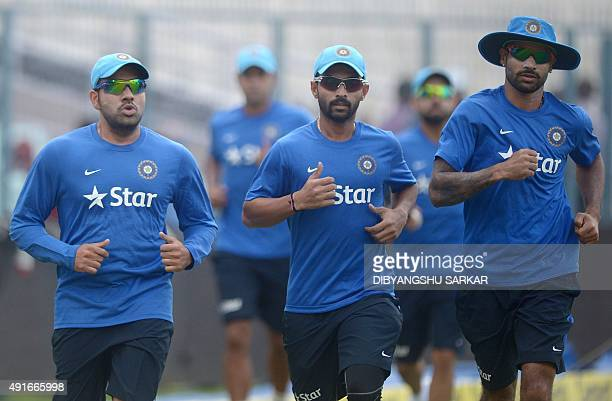 Indian cricketers Shikhar Dhawan Ajinkya Rahane and Rohit Sharma jog during a training session on the eve of the third T20 cricket match between...