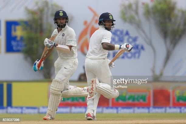 Indian cricketers Shikhar Dhawan and Cheteshwar Pujara run between the wickets during the 1st Day's play in the 1st Test match between Sri Lanka and...