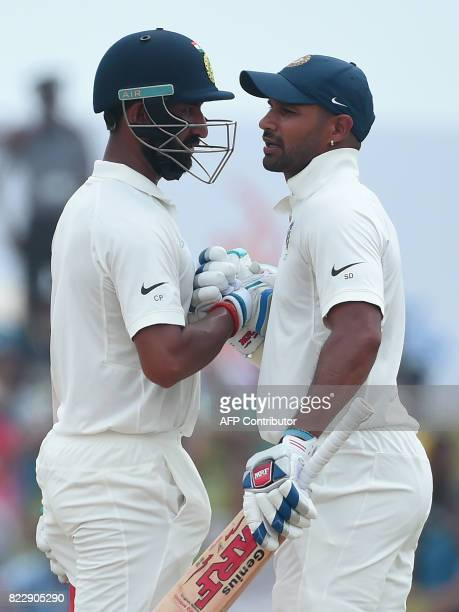 Indian cricketers Shikhar Dhawan and Cheteshwar Pujara talk during the first day of the first Test match between Sri Lanka and India at Galle...