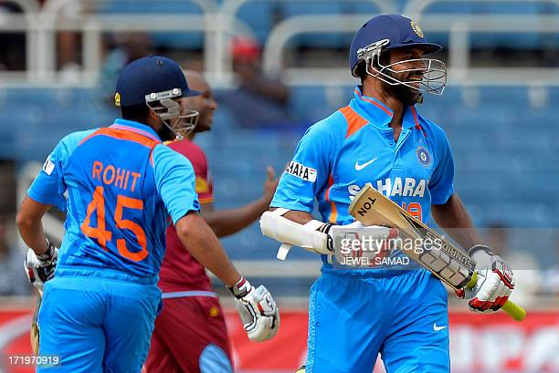 Indian cricketers Shikhar Dhawan smiles as he takes a run with teammate Rohit Sharma from a missfielding by West Indies players during the second...