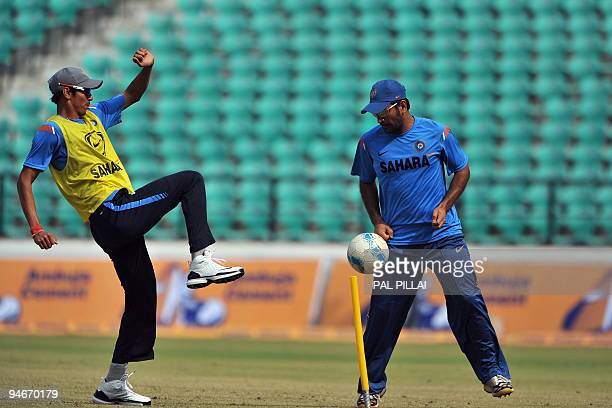 Indian cricketers Sudeep Tyagi and Mahendra Singh Dhoni play football during a practice session ahead of the second One Day International cricket...
