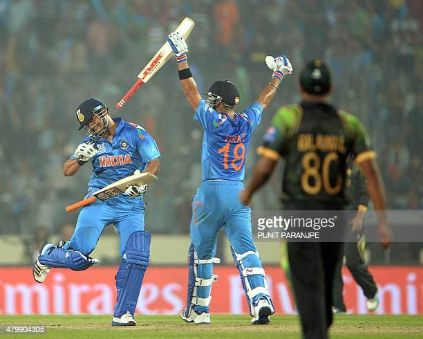 Indian cricketers Suresh Raina and Virat Kohli celebrate after winning the ICC World Twenty20 cricket match against Pakistan at The ShereBangla...