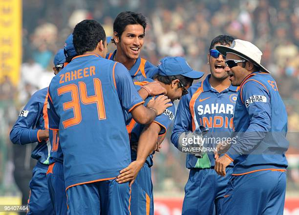 Indian cricketers surround teammate Suresh Raina as they celebrate the dismissal of unseen Sri Lankan batsman Thilan Samaraweera during the fifth and...