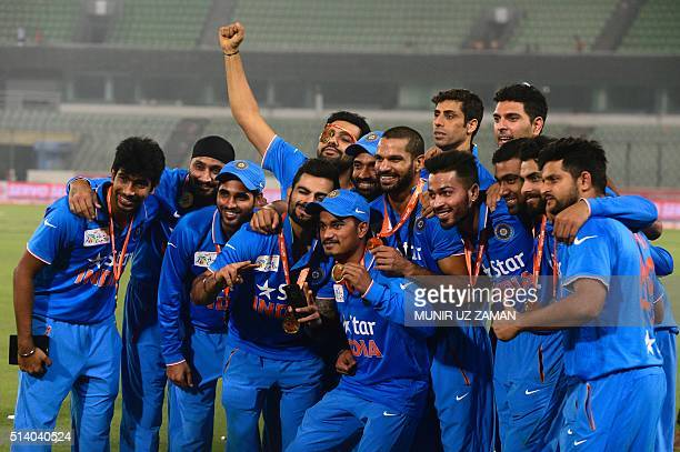 Indian cricketers take pictures with a mobile phone during the Asia Cup T20 cricket tournament final match between Bangladesh and India at the...