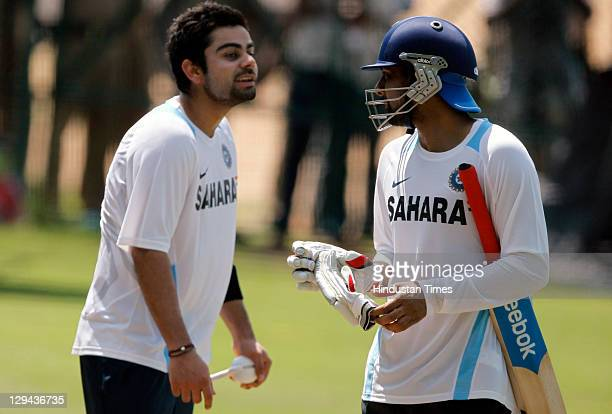 Indian cricketers Virat Kohli and Praveen Kumar having a chat during a practice session at Rajiv Gandhi Stadium on October 13 2011 in Hyderabad India