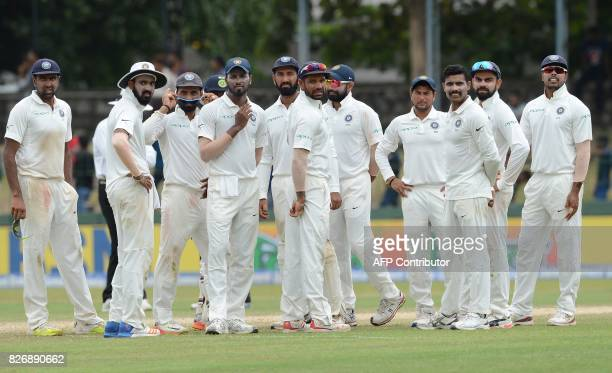 Indian cricketers wait for a third umpire review decision against Sri Lankan cricketer Niroshan Dickwella during the fourth day of the second Test...