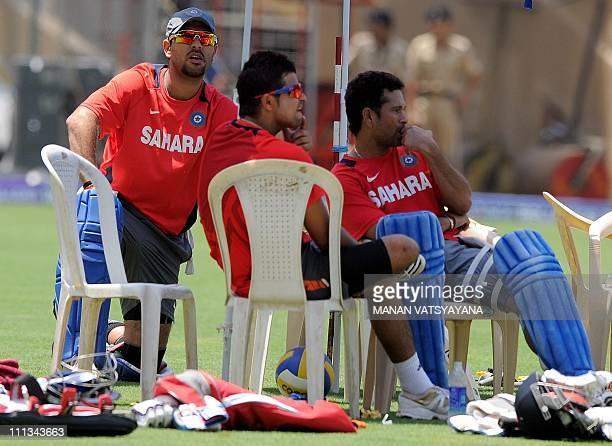Indian cricketers Yuvraj Singh Suresh Raina and Sachin Tendulkar take a break during a training session at The Wankhede Stadium in Mumbai on April 1...