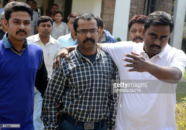 Indian Crime Investigation Department officials escort Child Welfare Officer Debashis Chandra from CID office in Siliguri on March 4 towards an...