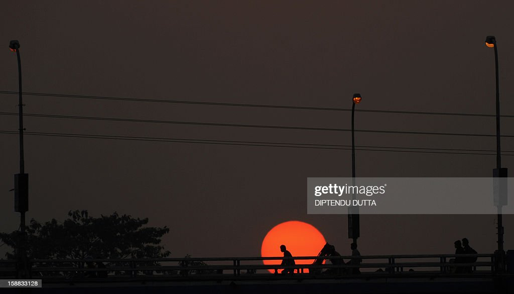 Indian cross a bridge as the sunsets in Siliguri on December 31, 2012. Sydney will kick off a wave of dazzling firework displays welcoming in 2013, from Dubai to Moscow and London, with long-isolated Yangon joining the global pyrotechnics for the first time. AFP PHOTO/Diptendu DUTTA