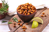 Traditional Indian cuisine. Roasted spicy chickpeas with lime and rosemary on rustic wooden background. Copyspace, horizontal view.