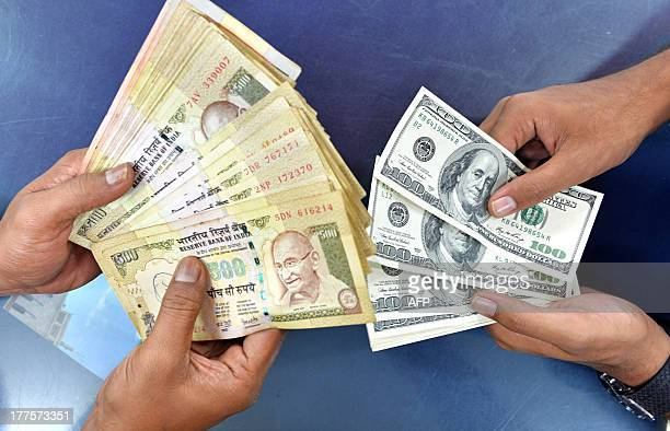 Indian customers at a foreign exchange outlet pose for a photo as they exchange Indian rupees for US dollars in Bangalore on August 24 2013 The rupee...