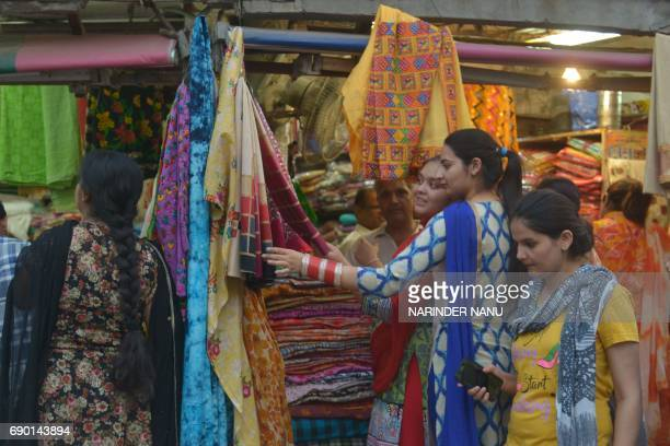 Indian customers browse at a shop selling women's suits and wedding outfits in a market in Amritsar on May 30 2017 / AFP PHOTO / NARINDER NANU