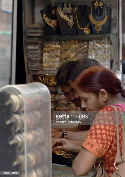 Indian customers browse items at a jewellery shop in New Delhi on May 8 2017 Fat wads of bank notes move across counters in Old Delhi's gold and...
