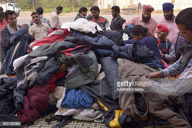 Indian customers browse through used winter clothes at a roadside stall in Amritsar on December 6 2015 Secondhand winter clothing is in heavy demand...