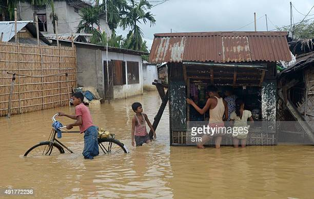 Indian customers buy essential items from a shop in a flooded street after a heavy downpour in Dimapur in the north eastern state of Nagaland on...