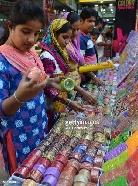 Indian customers inspect bangles on sale in Amritsar on October 4 2017 Bangles are in heavy demand ahead of the forthcoming Karva Chauth festival...