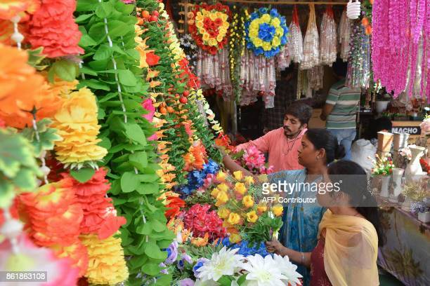 Indian customers look at artificial flower garlands ahead of Diwali festival at a roadside stall in Amritsar on October 16 2017 / AFP PHOTO /...