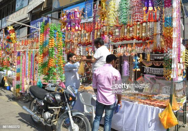 Indian customers look at decorative items ahead of Diwali festival at a roadside stall in Amritsar on October 16 2017 / AFP PHOTO / NARINDER NANU