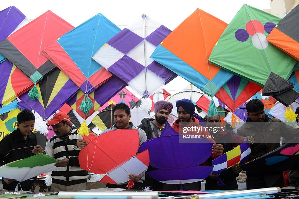 Indian customers look at kites on display at a kite stand in Amritsar on January 11, 2013. The demand for kites is rising on the eve of Lohri Festival. The festival is an annual thanksgiving day celebration and an extremely popular harvest festival in India, especially Northern India.