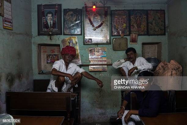 Indian customers look on as they sit inside a tea shop in Kekri some 78 kms south of Ajmer on May 13 in the northern state of Rajasthan / AFP PHOTO /...