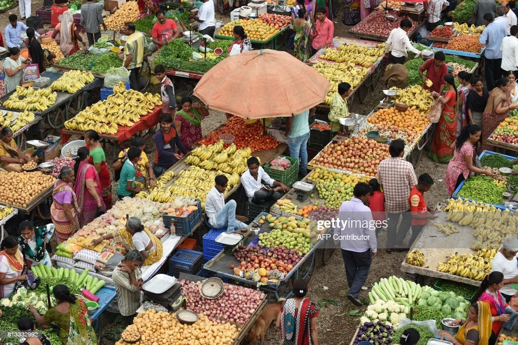 Indian customers shop and a fruit and vegetable market in Ahmedabad on July 12, 2017. /