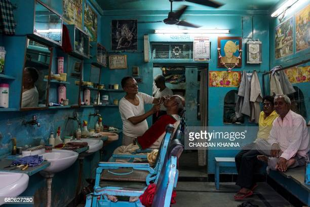 Indian customers wait their turn for a haircut inside a barber shop in Kekri some 78 kms south of Ajmer on May 13 in the northern state of Rajasthan...