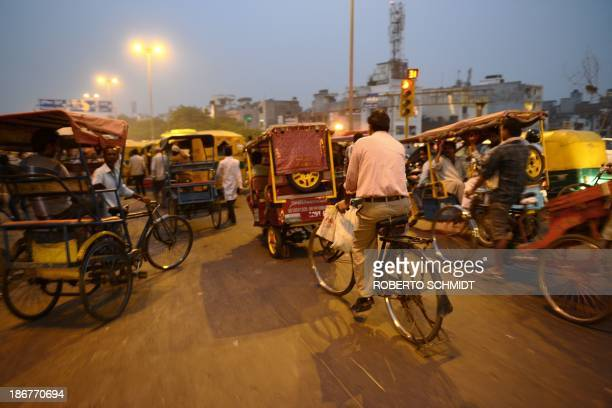 Indian cyclist Sushil Kumar pedals his bicycle among auto rickshaws in New Delhi on November 1 as he returns home after work Trucks and buses often...