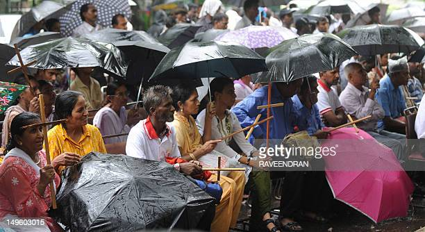 Indian Dalit untouchable Christians and Muslims sit in the rain during a protest rally against the National Commission for Scheduled Castes and...