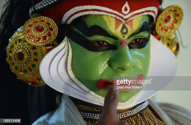Indian dancers from Kerala prepare their costumes backstage before preforming Kathakali a traditional dance in Ahmedabad on November 2 2012 Kathakali...