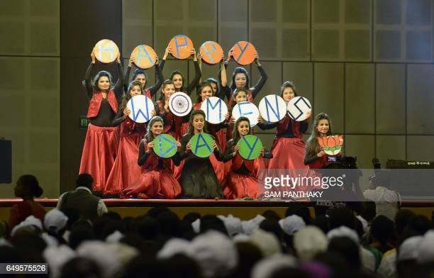 Indian dancers hold up sign that reads 'Happy Women's Day' at a 'Swachh Shakti 2017' award ceremony attended by Indian Prime Minister Narendra Modi...
