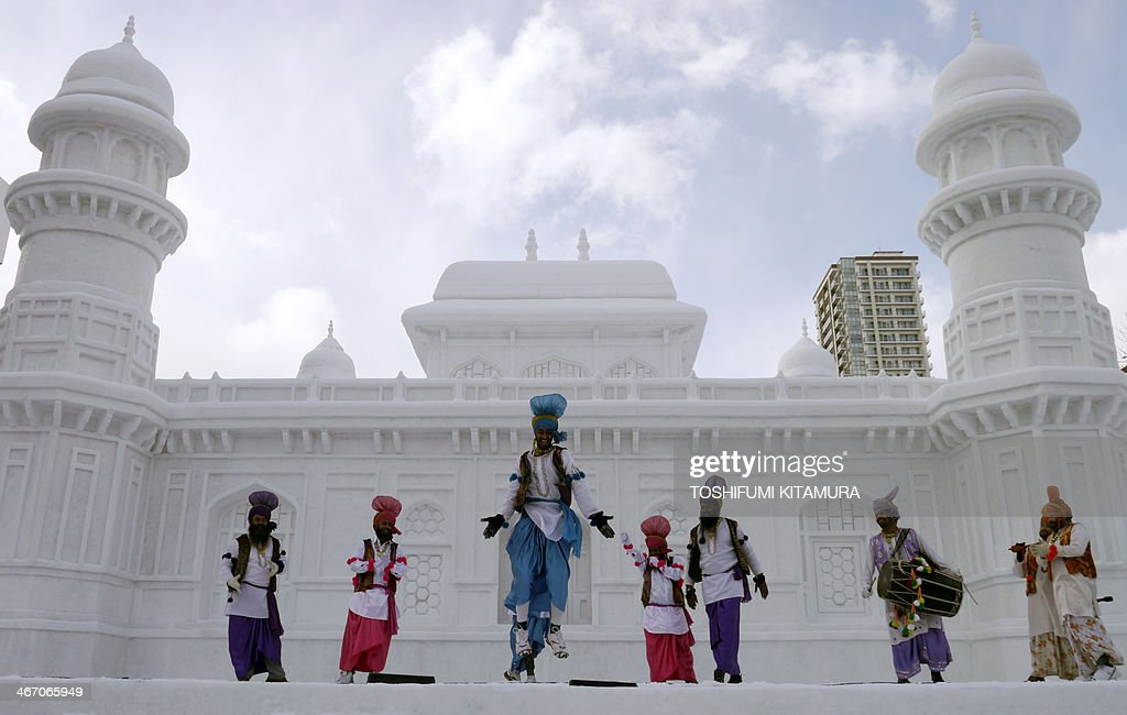 Indian dancers perform a Bhangra dance at the stage in front of the large snow sculpture of 'Tomb of Itmad-ud-Daula' of India during the 65th annual Sapporo Snow Festival in Sapporo on February 6, 2014. Nine foreign teams compete in the contest among some two million tourists expected to visit the week-long festival which started on Februrary 5.