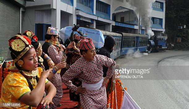 Indian dancers perform a routine while standing on a flatbed carriage of a 'toytrain' as a part of promotional event of The Darjeeling Tea and...