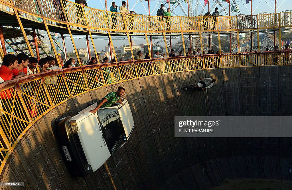 Indian daredevils perform car and bike stunts during an annual fair in Mumbai on January 3, 2013. The ten day-long fair is being held in honour of the Sufi saint Makhdoom Ali Mahimi on the dusty Mahim beach, which is full of people on giant wheels, toy trains and enjoying gravity-defying stunts in the 'Maut Ka Kuan' or 'Valley of Death'.