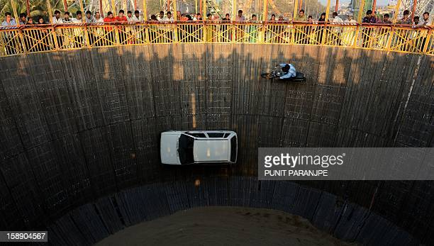 Indian daredevils perform car and bike stunts during an annual fair in Mumbai on January 3 2013 The ten daylong fair is being held in honour of the...