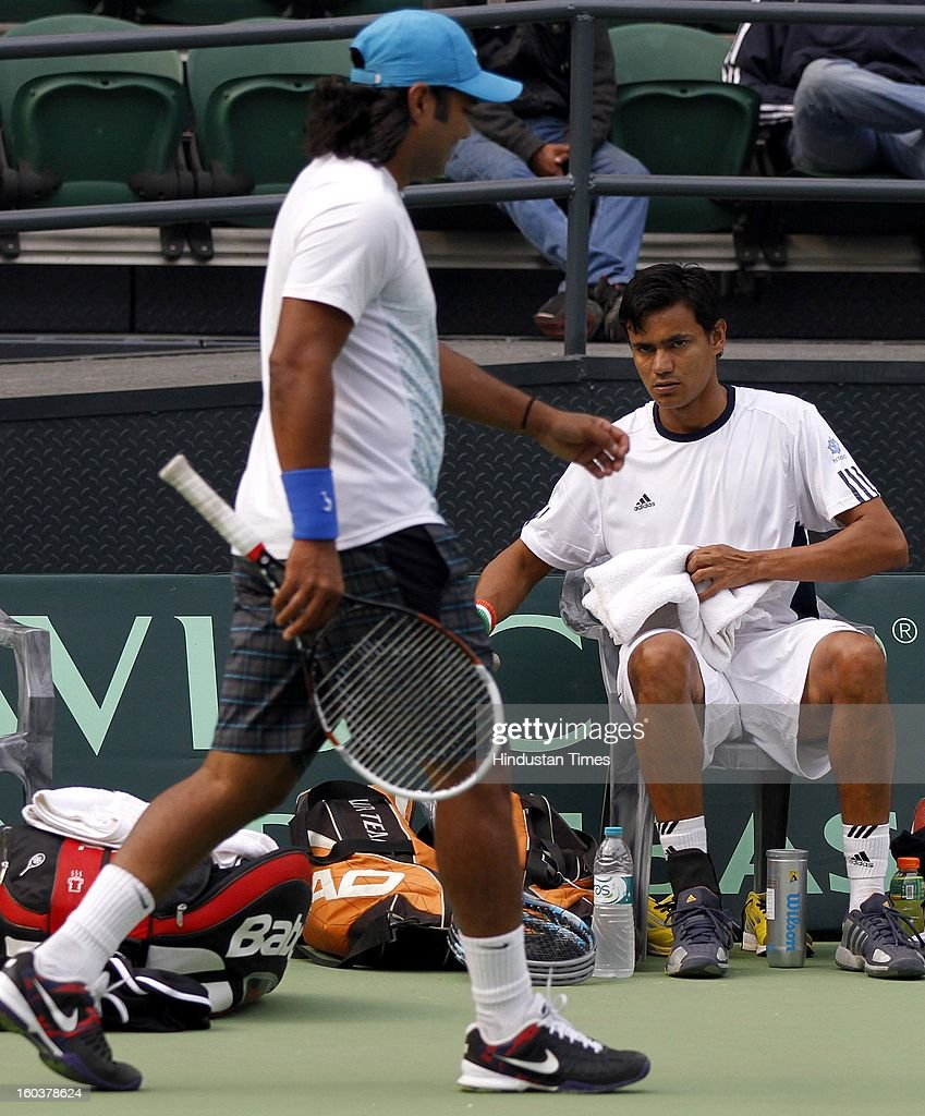 Indian Davis Cup player Vijayant Malik looks at Leander Paes during the practice session at DLTA on January 30, 2013 in New Delhi, India. After the rebellion by top Indian tennis players AITA has fielded an inexperienced team for the Davis Cup tie against South Korea that will begin on February 1.