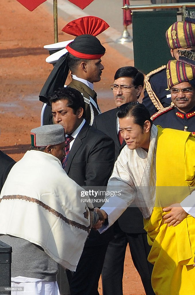 Indian Defence Minister A. K. Antony (L) welcomes Bhutan King Jigme Khesar Namgyel Wangchuk (R) during the Republic Day parade in New Delhi on January 26, 2013. India marked its Republic Day with celebrations held under heavy security, especially in New Delhi where large areas were sealed off for an annual parade of military hardware at which Bhutan's king Jigme Khesar Namgyel Wangchuck was chief guest.