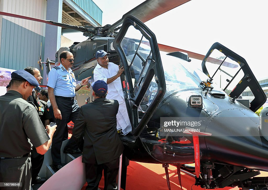 Indian defense minister A.K. Antony (R) gets into the cockpit of a HAL Rudra helicopter while Chief of Air Staff Air Chief Marshal N.A.K. Browne (C, in blue) looks on during Aero India 2013 at the Yelahanka Air Force station in Bangalore on February 6, 2013. The HAL Rudra is an armed version of the Dhruv multirole/utility helicopter manufactured by the Hindustan Aeronautics Limited company. India, the world's leading importer of weaponry, opened one of Asia's biggest aviation trade shows Wednesday with Western suppliers eyeing lucrative deals and a Chinese delegation attending for the first time. AFP PHOTO/Manjunath KIRAN