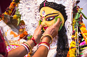 An Indian Deity : Goddess Durga during Durga Puja festival. Ladies bidding adieu to the mother Goddess on the last day of the festival , before immersion in a river.  Durga worship is a yearly event a