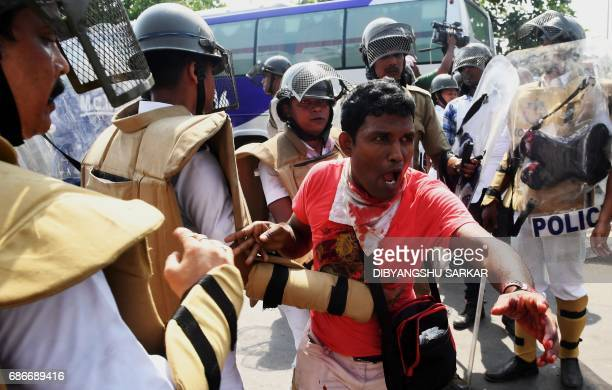 A Indian demonstrator reacts after being struck by a police baton during clashes between Leftist demonstrators and police during a march towards the...