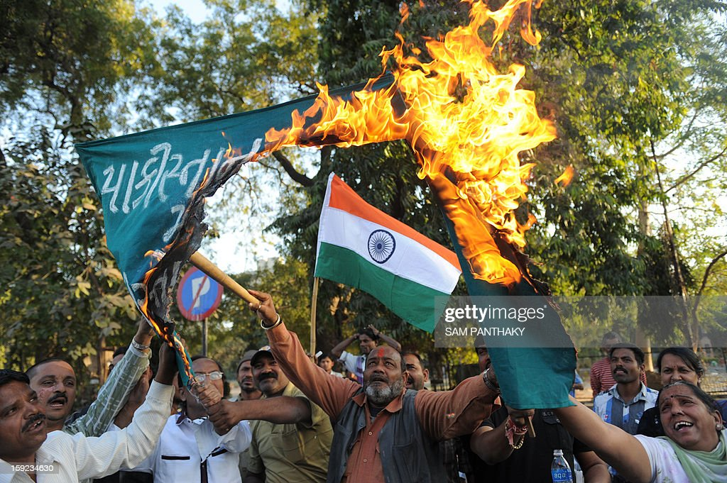 Indian demonstrators burn a banner which reads 'Down with Pakistan, Shame on Pakistan' as an Indian flag is pictured in the background as they demonstrate against the alleged killing of two Indian soldiers by Pakistan in the disputed Kashmir region, in Ahmedabad on January 10, 2013. Pakistan on January 10 accused Indian troops of opening fire and killing a Pakistani soldier, the third deadly cross-border incident in days that threatens to escalate tensions in Kashmir. AFP PHOTO / Sam PANTHAKY