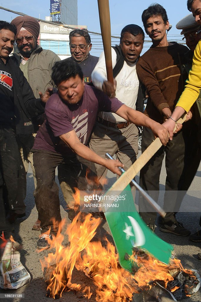 Indian demonstrators burn a representation of the Pakistani flag during a protest against the death of two Indian soldiers in the disputed Kashmir region, in Amritsar on January 10, 2013. Pakistan on January 10 accused Indian troops of opening fire and killing a Pakistani soldier, the third deadly cross-border incident in days that threatens to escalate tensions in Kashmir. AFP PHOTO/NARINDER NANU