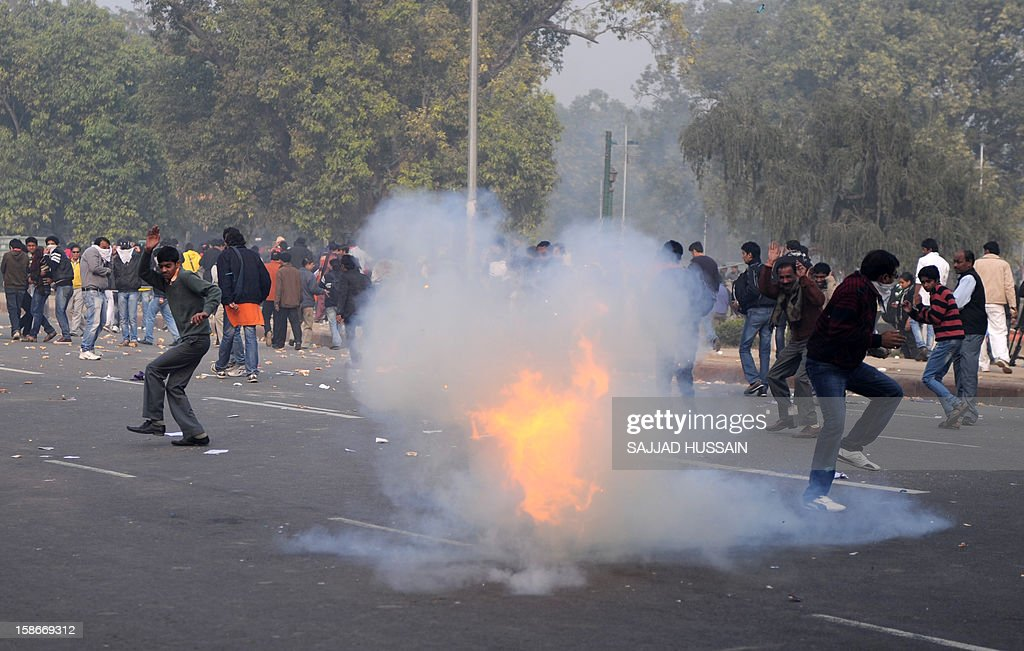 Indian demonstrators react after a tear gas canister explodes during a protest calling for better safety for women following the rape of a student last week, in front the India Gate monument in New Delhi on December 23, 2012. In the biggest protest so far, several thousand college students rallied at the India Gate monument in the heart of the capital where they were baton-charged, water cannoned and tear gassed by the police. AFP PHOTO/ Sajjad Hussain
