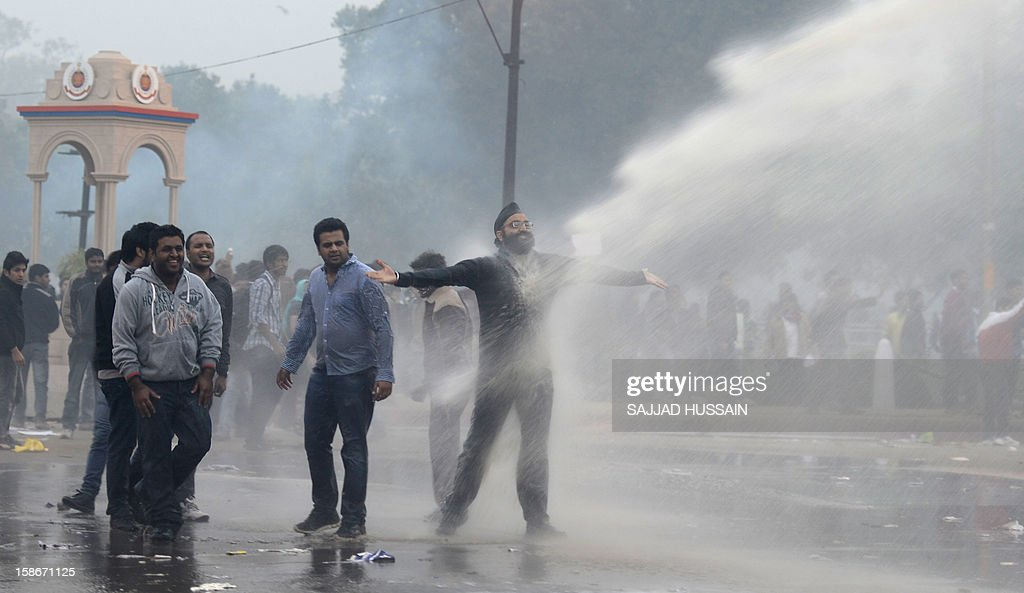 Indian demonstrators taunt police spraying them with water cannons during a protest calling for better safety for women following the rape of a student last week, in front the India Gate monument in New Delhi on December 23, 2012. In the biggest protest so far, several thousand college students rallied at the India Gate monument in the heart of the capital where they were baton-charged, water cannoned and tear gassed by the police. AFP PHOTO/ Sajjad Hussain