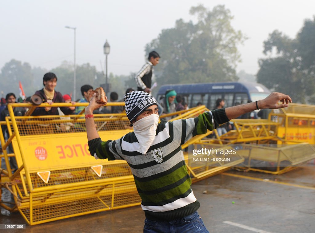 Indian demonstrators throw stones at police during a protest calling for better safety for women following the rape of a student last week, in front the India Gate monument in New Delhi on December 23, 2012. In the biggest protest so far, several thousand college students rallied at the India Gate monument in the heart of the capital where they were baton-charged, water cannoned and tear gassed by the police. AFP PHOTO/ Sajjad Hussain