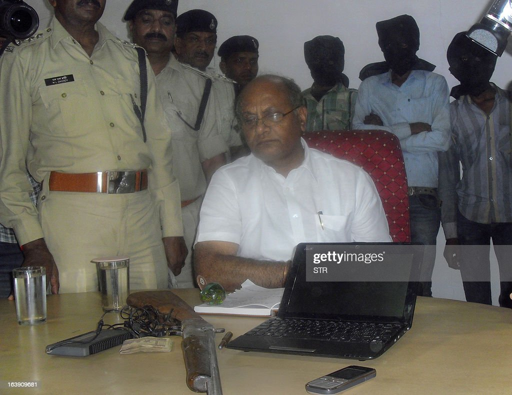 Indian Deputy Inspector General DK Arya (C) displays recovered goods including a laptop and mobile as three of five hooded suspects are seen in the background during a press meeting in Datia, about 75 kms from Gwalior in central Madhya Pradesh state on March 17, 2013. Police in India said Sunday they had arrested a group of farmers in their twenties who had confessed to gang-raping a Swiss cyclist, the latest in a series of shocking sex crimes in the country. AFP PHOTO